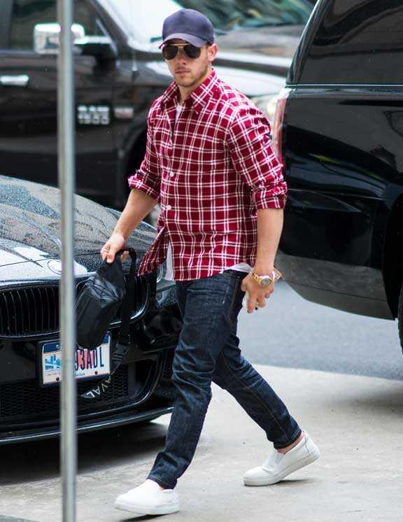 パリっとした赤シャツにリジットな濃紺デニム&濃紺キャップ。ニックらしい清潔感ある都会的なカジュアルコーデだ。これがこなれて見えるのは、無造作に捲り上げた袖と爽やかなヌケ感を作ったシンプル白スニ。