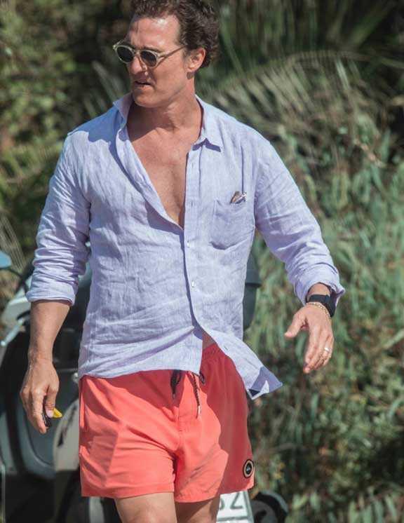 海好きマシューの今年の水着は、ショート丈のサンセットカラー。確かにこれは今年らしい1枚。そこに、Tシャツではなく爽やかな青リネンシャツを無造作に合わせるなんて、さすがの洒落者。実に大人らしいリゾートコーデ。